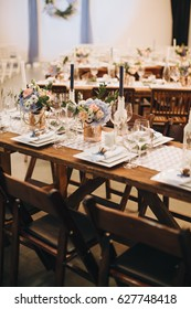 The wooden festive table is decorated with compositions of flowers, candles and served with cutlery, glasses and plates