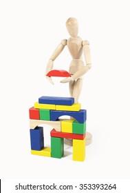 Wooden figure builds house of bricks