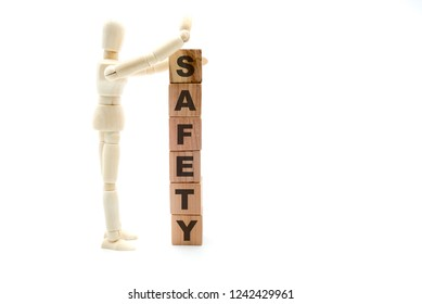 Wooden figure as businessman building Safety as tower of wood cubes, isolated on white background, minimalist concept