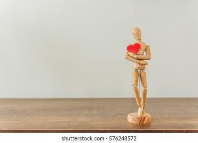 Wooden figure holding heart