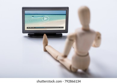 Wooden Figure Holding Remote Watching Video On Television
