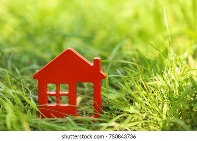 Wooden figure of house on green grass