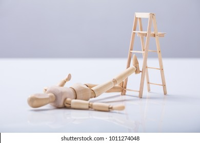 Wooden Figure Lying On Floor After Falling From Ladder