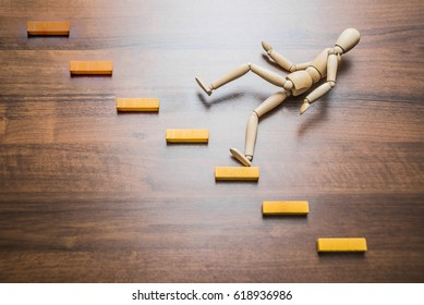 wooden figure man falling down from stairs, accident, concept,  failure, collapse and fiasco in business idea.