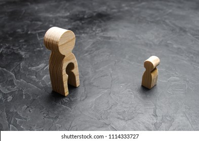 A wooden figure of a man with a void in the form of a child inside the body stands and looks at the child. The concept of infertility in women, the loss of a child. Adoption, reunification. A family.