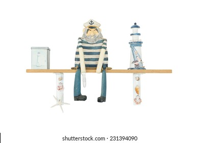 Wooden Figure of Sailor Man or Ship Captain isolated on white, sitting on plank decorated with lighthouse and shells. Travel and adventure concept