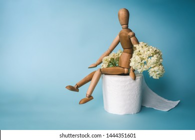Wooden figure sit on a roll of toilet paper and flower of buldenege on a blue background. Toilet paper with a smell. Concept of the problem with digestion.