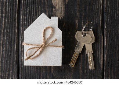 Wooden figure of white house and keys on a dark wooden background