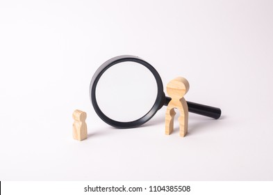 A wooden figure of a woman and a child stands near the magnifying glass. The concept of finding a child, the adoption of children. Mother lost her baby and is now looking for him.