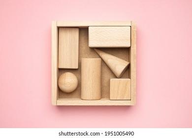 hölzerne Figuren in einer Schachtel auf rosafarbenem Hintergrund. Abstrakter Hintergrund von Holzobjekten. Geometrische Zusammensetzung. Draufsicht mit geometrischen Formen