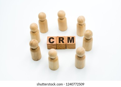 Wooden figures as business team in circle around acronym CRM Customer Relationship Management, isolated on white background, minimalist concept