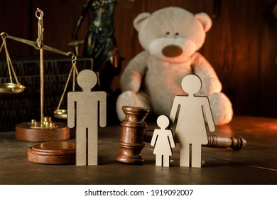Wooden figures of family with teddy bear and gavel in a courtroom. Divorce and alimony concept
