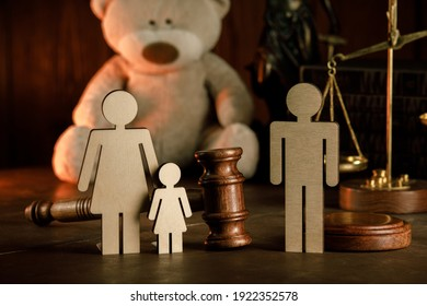Wooden figures of family with teddy bear and gavel on a table close-up. Divorce and alimony concept