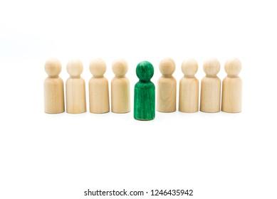 Wooden figures in line as business team, with one green figure standing out from the crowd, isolated on white background. Conceptual image of being different