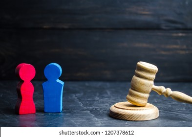wooden figures of a man and a woman are standing near the judge's gavel. inequality concept : gender pay gap. divorce. Division of property in court. Social role in the family