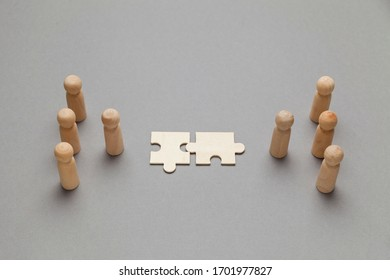 Wooden figures with pazzles on grey background. Agreement between business mans, cooperation and deal concept. Successful contract.