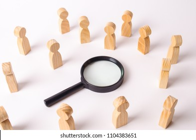 Wooden figures of people stand around the magnifying glass and look to the center. The concept of the search for people and workers, human resources. Hiring for work, tracing people.