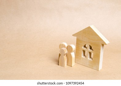 Wooden figures of persons stand near a wooden house. Family is standing near the house. The concept of a couple in love, cohabitants, parents, buyers and sellers at home. They live in house