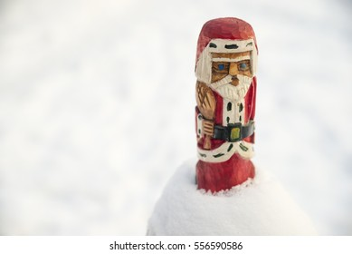 Wooden figurine of Santa Claus sitting in the snow