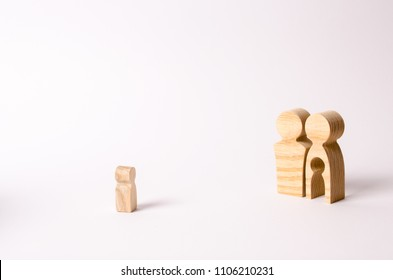 Wooden figurines of parents look at a lonely child. An orphan child is looking for a family. A barren couple adopts abandoned children. Loss of a single child. Medical problems. couple wants a baby.