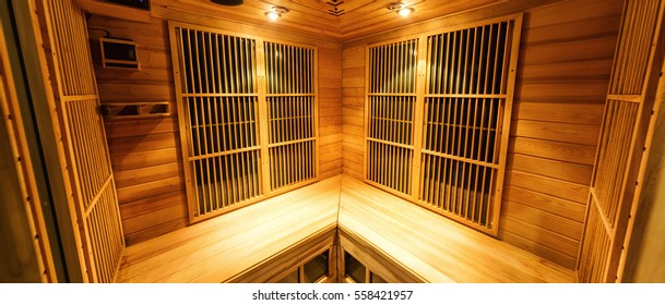 Wooden finnish (infrared dry) sauna room with traditional accessories