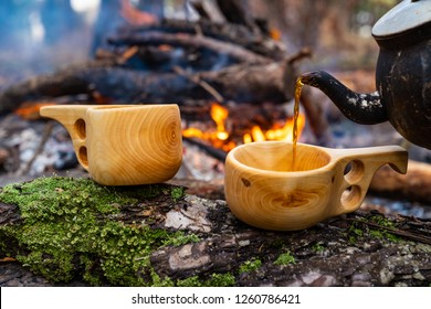 wooden finnish mug, called Kuksa on the stump, with camp fire