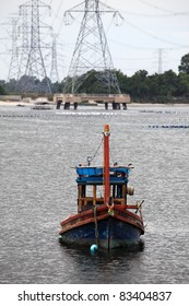 Wooden fishing boat and electrical tower in industrial area