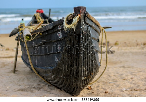 Wooden fishing boat on the shore of Tajpur beach. Shot with shallow depth of field to create blurry effect.