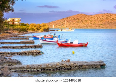 Wooden fishing boat and yachts anchored at the tropical waters of the famous gulf of Elounda, the village of celebrities, near Spinalonga, Crete, Greece.