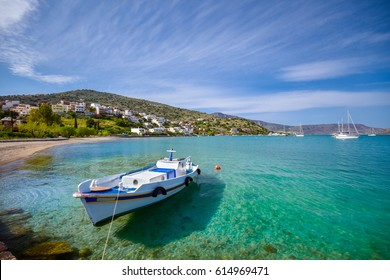 Wooden fishing boat and yachts anchored in the tropical gulf of famous Elounda, Crete, Greece.