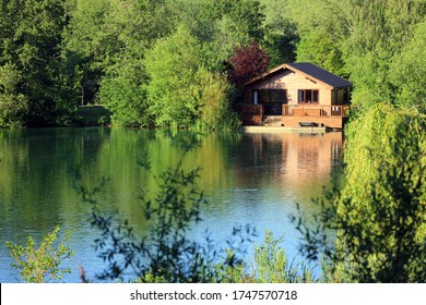 A Wooden Fishing Lodge On The Banks Of A Cotswold Leisure Lake. UK