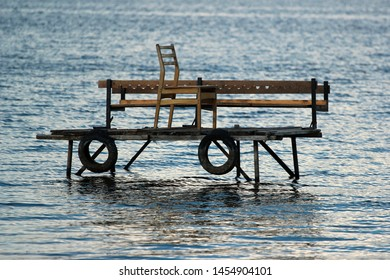 Wooden fishing platform in water, with tire fenders and chair