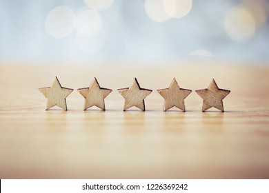 Wooden five star shape on table. The best excellent business services rating customer experience concept.