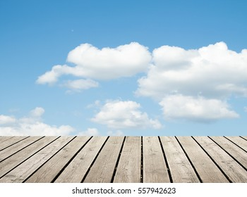 wooden floor against the sky with clouds