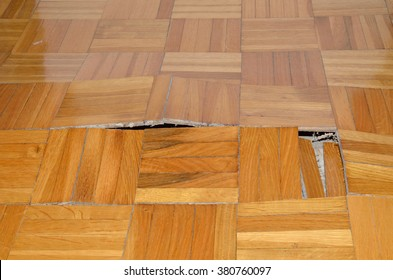 Wooden floor in apartment with floor damaged by destructive elements such as wet, moisture, water.
