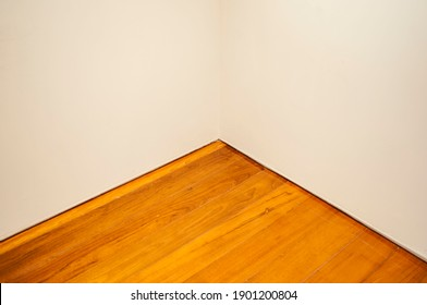 The wooden floor of the corner of the white room.