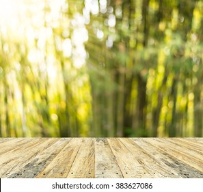 Wooden floor and green nature bokeh on sunlight for background