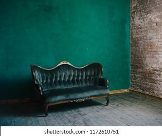 wooden floor in luxury green room. emerald velvet sofa in livingroom. luxury place for relax. brick wall in loft interior