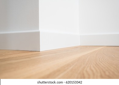wooden floor parquet and white walls closeup