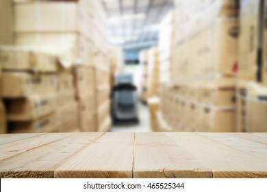 Wooden floor or wooden table with blurred image of warehouse for background.