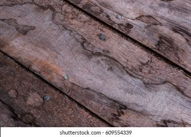 Wooden floorboards with distinct patterns in a diagonal direction and nail heads with grains of sand in gaps between boards