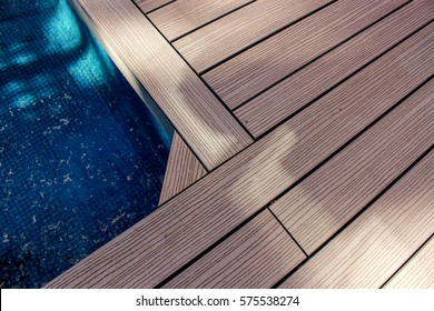 Wooden floors for outdoor swimming pool with blue water inside