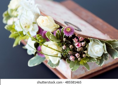 Wooden flower box arrangement with white roses. Small depth of field.