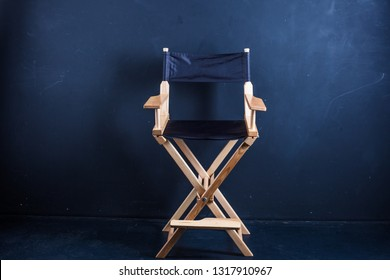 Wooden folding chair for movie director. Vintage, black fabric on a black background. Portable chair.