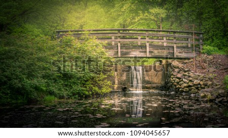 Wooden foot bridge over a spillway in the early morning