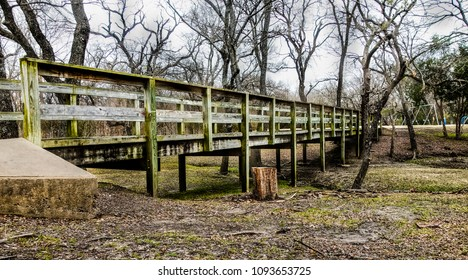 Wooden footbridge crossing a dry creek bed at a city park in the fall