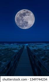 Wooden footbridge at night with supermoon
