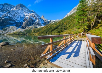 Wooden footbridge on path along Morskie Oko lake in autumn colours with fresh snow covered peaks, High Tatra Mountains, Poland