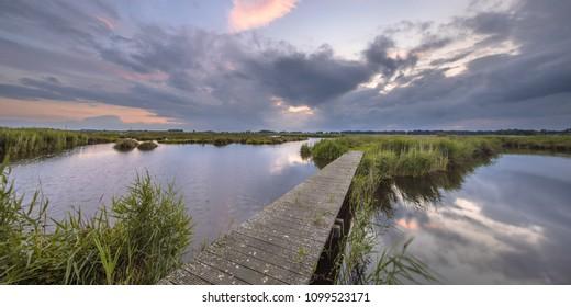 Wooden footbridge over river as a concept for challenge in nature reserve de Onlanden near Groningen, Netherlands