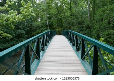 Wooden footpath bridge with metal handrails crossing creek through forest perspective